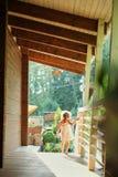Porträt eines kleinen Mädchens, das draußen entlang die Veranda, Sonnenscheinsommer, das Mädchen geht, geht spazieren lizenzfreie stockfotos