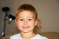 Porträt eines kleinen Mädchens, das von Ohr zu Ohr lächelt Lizenzfreies Stockfoto