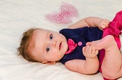 Porträt eines kleinen Mädchens in einem Kleid in einer Windel, die auf dem Bett in ihrem Raum liegt Lizenzfreie Stockfotos
