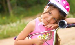 Porträt eines kleinen Mädchens in einem Schutzhelm steuert ihr Fahrrad und hält einen Blumenstrauß von Gänseblümchen stockfotos