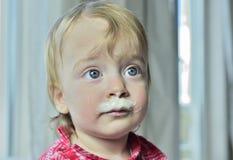 Porträt eines kleinen Mädchens mit den Milchschnurrbärten Lizenzfreies Stockbild
