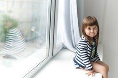 Porträt eines kleinen Mädchens sitzt auf einem Fensterbrett stockfotos
