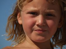 Porträt eines kleinen missfallenen Mädchens auf Hintergrund des blauen Himmels stockfotografie