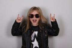 Porträt eines kleinen Schwermetallmädchens mit Sonnenbrille Nettes kleines Mädchen, das ein Stein-nrollenzeichen macht Lizenzfreies Stockfoto