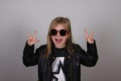 Porträt eines kleinen Schwermetallmädchens mit Sonnenbrille Nettes kleines Mädchen, das ein Stein-nrollenzeichen macht Lizenzfreie Stockfotografie