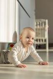 Porträt eines lächelnden Babys, das auf eine ändernde Tabelle legt Stockfotos