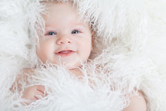 Lächelndes Baby eingewickelt in einem weißen Pelz. Lizenzfreies Stockfoto