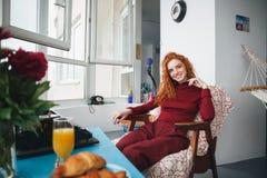 Porträt eines lächelnden hübschen Mädchens, das auf einem Stuhl sitzt Stockfotografie