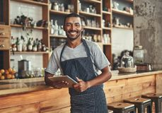 Porträt eines lächelnden jungen afrikanischen Caféinhabers stockfotos