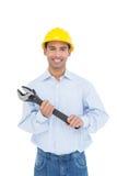 Porträt eines lächelnden jungen Heimwerkers, der einen Schlüssel hält Stockfoto