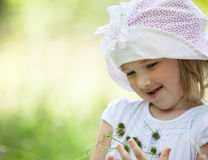 Porträt eines lächelnden kleinen Mädchens, das wilde Blumen hält Stockfoto