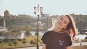 Porträt eines lächelnden Mädchens auf dem Hintergrund der Stadt an einem Sommertag stock video