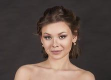 Porträt eines lächelnden Mädchens auf einem dunklen Hintergrund Stockfotos