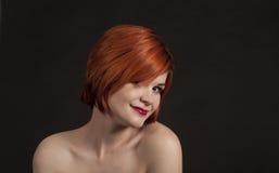Porträt eines lächelnden Mädchens auf einem dunklen Hintergrund Lizenzfreies Stockfoto