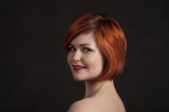 Porträt eines lächelnden Mädchens auf einem dunklen Hintergrund Stockbilder