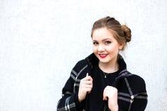 Porträt eines lächelnden Mädchens im hohen Schlüssel gegen weiße Wand Stockfotografie