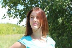 Porträt eines lächelnden Mädchens mit Naturhintergrund des dunklen Haares Ionen stockbild
