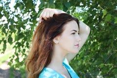 Porträt eines lächelnden Mädchens mit Naturhintergrund des dunklen Haares Ionen stockbilder