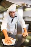 Porträt eines lächelnden männlichen Kochs, der Küchenarbeitsplatte abwischt Stockfotografie