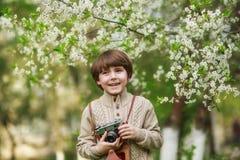 Porträt eines lächelnden netten Jungen, der Foto mit Retro- Kamera macht Lizenzfreie Stockbilder