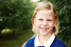 Porträt eines lächelnden Schulmädchens in einem blauen Kleid Stockfotos