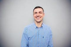 Porträt eines lachenden Mannes über grauem Hintergrund Stockbild