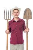 Porträt eines Landwirts in einem Hut mit einer Heugabel und einer Schaufel Stockbild