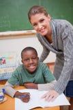 Porträt eines Lehrers, der etwas einem lächelnden schoolbo erklärt lizenzfreies stockfoto