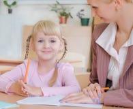 Porträt eines Lehrers, der etwas einem lächelnden schoolgi erklärt stockbilder