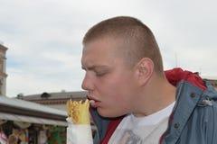 Porträt eines lustigen Kerls, der shawarma mit Vergnügen isst stockfotos