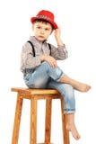 Porträt eines lustigen kleinen Jungen, der auf einem hohen Schemel in einem Rot sitzt Lizenzfreies Stockfoto