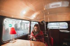 Porträt eines Mädchens, das in der Kaffeestube am Tisch, bedeckt mit einer Decke, einen Tasse Kaffee in ihrer Hand halten sitzt stockfoto