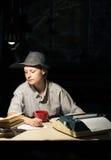 Porträt eines Mädchens, das an einem Tisch mit einer Schreibmaschine und Büchern, Anmerkungen nachts machend sitzt Stockbilder