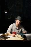 Porträt eines Mädchens, das an einem Tisch mit einer Schreibmaschine und Büchern, Anmerkungen nachts machend sitzt Stockbild