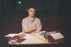 Porträt eines Mädchens, das an einem Tisch mit einer Schreibmaschine und Büchern sitzt, denken an die Idee nachts Stockbild