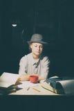 Porträt eines Mädchens, das an einem Tisch mit einer Schreibmaschine und Büchern sitzt, denken an die Idee nachts Lizenzfreies Stockbild