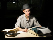 Porträt eines Mädchens, das an einem Tisch mit einer Schreibmaschine und Büchern sitzt, denken an die Idee nachts Lizenzfreies Stockfoto