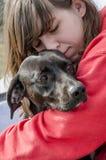 Porträt eines Mädchens, das einen Hund umarmt stockbild