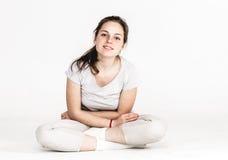 Porträt eines Mädchens der recht jungen Frau, das auf dem Boden lokalisiert auf Weiß sitzt Lizenzfreie Stockfotografie