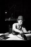 Porträt eines Mädchens in einem Hut, der an einem Tisch sitzt und auf einer Schreibmaschine nachts schreibt Stockfotografie