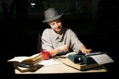 Porträt eines Mädchens in einem Hut, der an einem Tisch sitzt und auf einer Schreibmaschine nachts schreibt Lizenzfreie Stockfotografie