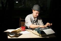 Porträt eines Mädchens in einem Hut, der an einem Tisch sitzt und auf einer Schreibmaschine nachts schreibt Lizenzfreies Stockbild