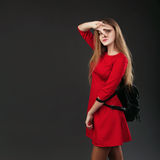 Porträt eines Mädchens in einem roten Kleid mit einem schwarzen ledernen Rucksack lizenzfreies stockbild
