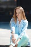 Porträt eines Mädchens in einer blauen Klage, sitzend nahe dem Büro stockfoto