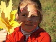 Porträt eines Mädchens in einer roten Strickjacke auf deren Gesicht eine Gesichtsmalerei und der Schatten von Ahornblättern stockfotografie