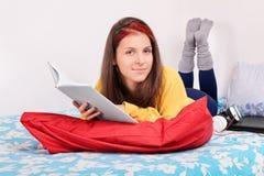 Porträt eines Mädchens in ihrem Bett ein Buch lesend Stockbilder