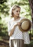 Porträt eines Mädchens mit einem Strohhut in den Händen stockbild