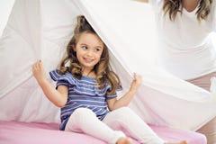 Porträt eines Mädchens unter Abdeckungen durch weißes Blatt stockfoto
