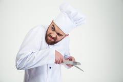 Porträt eines männlichen Chefkochs, der Messer I schärft Stockbilder