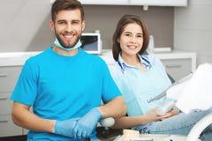 Porträt eines männlichen Zahnarztes und des jungen glücklichen weiblichen Patienten stockfoto